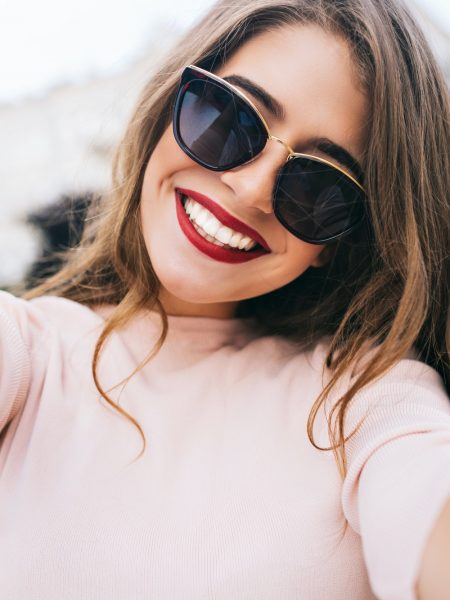 closeup-selfie-portrait-of-attractive-girl-in-sunglasses-with-long-hairstyle-and-snow-white-smile-in